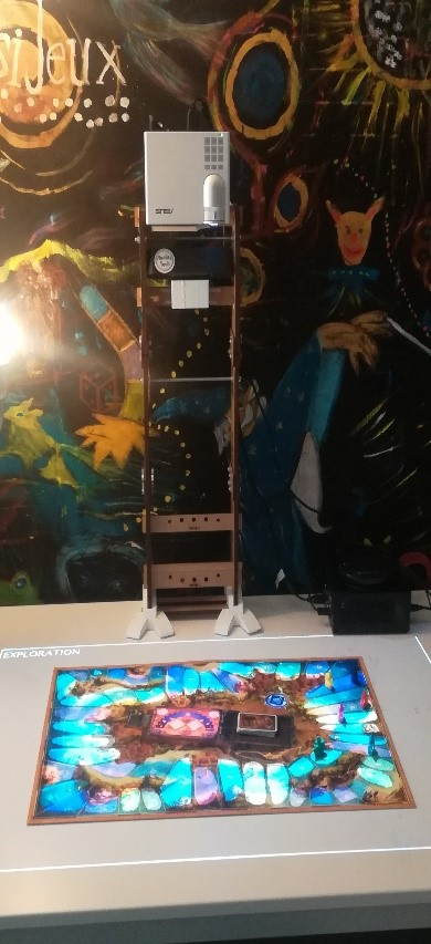 Photo of the Papart tool: wooden tower about 80 centimeters high on which a video projector is installed. This video projector illuminates the game board placed on a table.